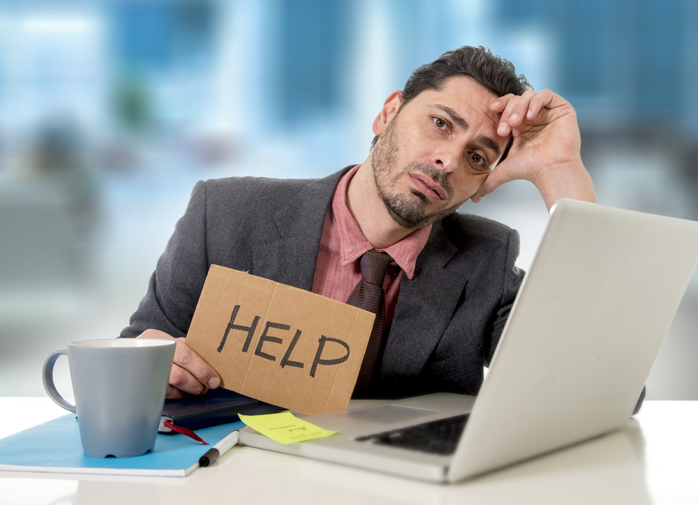 young businessman at office desk working on computer laptop asking for help holding cardboard sign looking desperate and depressed in business stress overwhelmed and overwork concept