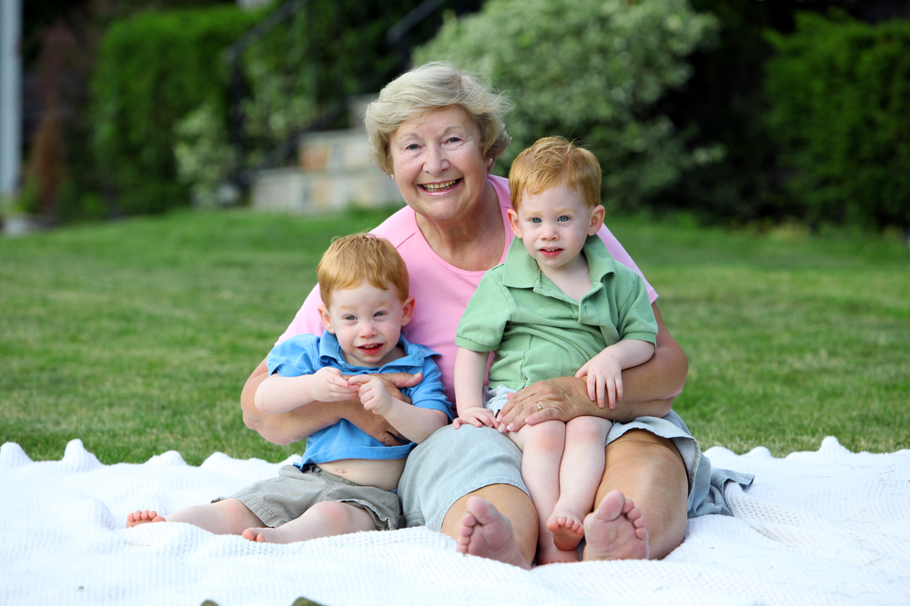 Happy grandmother holding twin boys