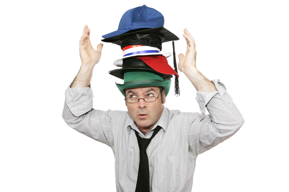A businessman overwhelmed by too much responsibility - wearing too many hats. Isolated on white.